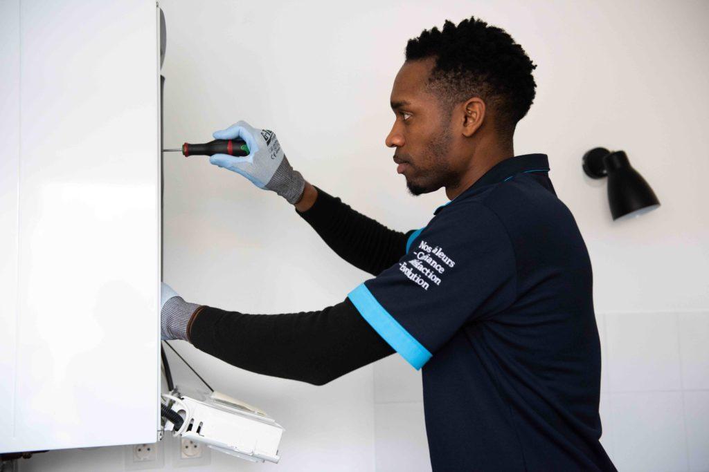 Technicien chauffagiste EFFICA SERVICE réalisant l'entretien et la maintenance d'une chaudière à gaz