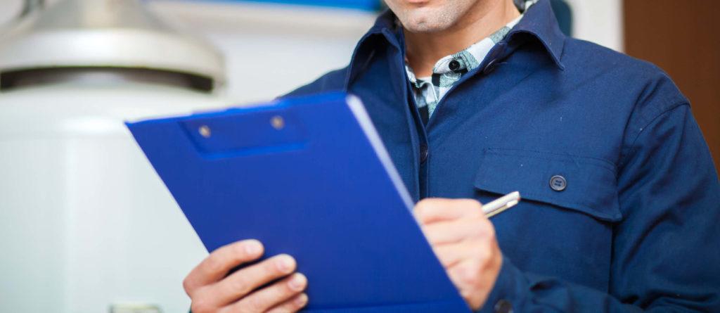 technicien chauffagiste devant une chaudière lors d'un entretien maintenance de chauffage